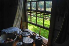 Offenes Fenster auf einem Sommer-Sagen mit antiken T?pfen und Sch?sseln stockbilder