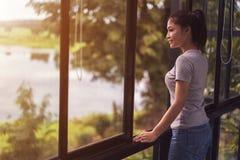 Offenes Fenster der Frau und Schauen zur Natur stockfotografie