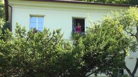 Offenes Fenster des weiblichen Hausmeisters und Wasserblumentöpfe auf Fensterbrett auf zweitem Hausboden 4K stock video
