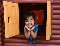 Offenes Fenster und Lächeln des asiatischen Mädchens Lizenzfreie Stockbilder