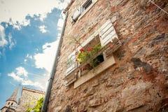 Offenes Fenster verziert mit Blumentöpfen am alten Steingebäude Lizenzfreies Stockfoto