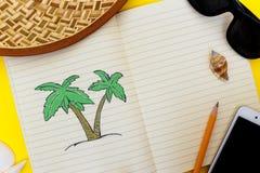 Offenes Notizbuch mit einem Bild einer Palme liegt auf einer ausdrucksvollen gelben Oberfläche, die durch verschiedene Gegenständ Stockbilder