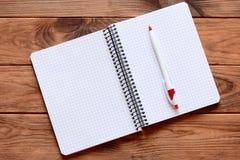 Offenes Papiernotizbuch des freien Raumes für das Schreiben von Anmerkungen, Stift lokalisiert auf hölzernem Hintergrund Papierno Lizenzfreie Stockfotos