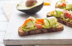 Offenes Sandwich oder Toast Kornbrot mit Lachsen, Weißkäse, Avocado, Gurke und Spinat Gesunder Snack, gesundes Fett und Omega stockfotos