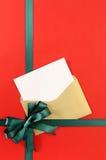 Offenes Weihnachten oder Glückwunschkarte mit grünem Geschenkbandbogen auf dem einfachen roten Packpapierhintergrund, vertikal Stockfotografie