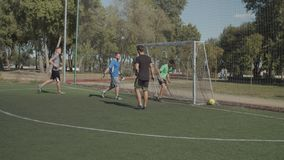 Football striker scoring a goal during match. Offensive football players moving towards opponent goal by passing the ball and creating opportunity for scoring stock footage