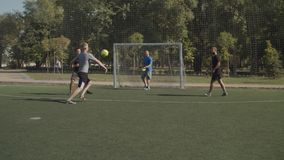 Offensive football team missing a goal during game. Offensive street football team missing a goal during soccer game. Young soccer player taking a shot on target stock footage