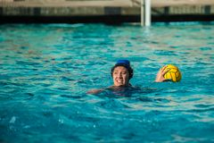 Offensive player looking for scoring opportunity. Water polo female athlete showing intense expression as she searches for a teammate to pass the ball Stock Photo