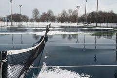Offentlig hård tennisbana som täckas med snö och vatten Arkivfoto