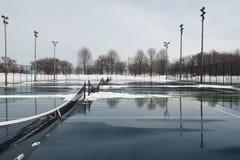 Offentlig hård tennisbana som täckas med snö och vatten Arkivfoton