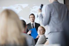 Offentlig högtalare som ser affärskvinnan som svarar under seminarium Royaltyfria Foton