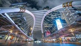 Offentlig Skywalk för Chong Nonsi Bangkok Sky Train station bro med de moderna byggnaderna på bakgrund på natten stock video