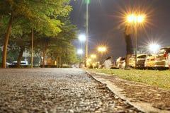 Offentligt parkera på natten, och folket att jogga som för övning sitter, kopplar av arkivfoton