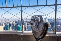 Offentligt teleskop som pekas på Manhattan byggnader Arkivbild