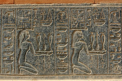 Offer. Kneeling women making offerings of precious unguents. Carving in black granite on Hatshepsut's red chapel at Karnak royalty free stock images
