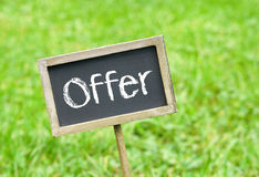 Offer - chalkboard with text on green grass background. Offer - wooden chalkboard with text on green grass background royalty free stock images