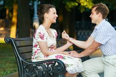 Offer of marriage outdoors. Young smiling man making offer of marriage and giving gold ring to woman oundoors Stock Images