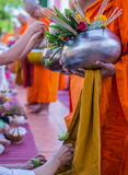 Offer sacrifice flowers to monk. Offer sacrifice flowers to Buddhist monk Royalty Free Stock Image