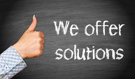 We offer solutions. Hand of businesswoman with thumb up and words we offer solutions written on blackboard Royalty Free Stock Photography