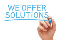 We Offer Solutions Blue Marker. Hand writing We Offer Solutions with blue marker on transparent glass board Royalty Free Stock Photos