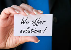 We offer solutions. A closeup of a hand holding up a card with the text We offer solutions Royalty Free Stock Photos