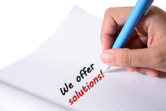 We offer solutions. Hand holding blue pen writing we offer solutions in black and red ink on white paper Royalty Free Stock Photo