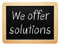 We offer solutions sign. We offer solutions written on blackboard or chalkboard, isolated on white background Stock Images