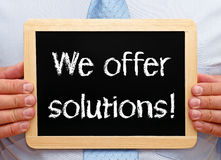 We offer solutions. Written on blackboard held by businessman Royalty Free Stock Images