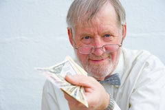 Offer to pay in Dollars. An image of a smiling Senior with bow tie and spectacles  offering to pay for goods or a ticket in US Dollars. An image of ' cash in Stock Photos