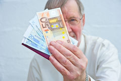 Offer to pay in Euros. An image with selective focus of a Senior offering to pay for an airline  ticket in Euros Royalty Free Stock Image