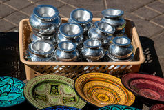 Offer of traditional products, Morocco. Offer on the path: basket full of silver ashtrays and various colors and decorations of the traditional plates Royalty Free Stock Photo