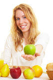 Offering an apple. Woman at the breakfast table eating an apple stock photos