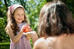 Offering apple - mother with child Stock Photos