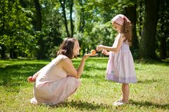 Offering apple - mother with child. Offering apple - young mother with child outdoor in nature Stock Image