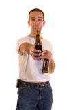 Offering A Beer. A young man offering someone a beer Royalty Free Stock Images