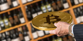 Offering bitcoin for bottles of wine in store. Businessman offering a bitcoin in payment for bottles of wine in wine store or supermarket in concept for e Royalty Free Stock Photos