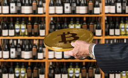 Offering bitcoin for bottles of wine in store. Businessman offering a bitcoin in payment for bottles of wine in wine store or supermarket in concept for e Stock Image