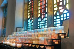 Offering candles in front of a stained glass window at Aylesford Priory. Offering candles glow infront of stained glass windows at Aylesford Priory stock photo