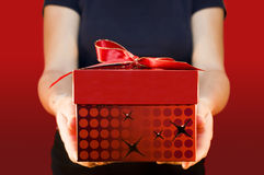 Offering a gift. Man holding and offering a gift to someone Royalty Free Stock Photography