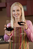 Offering a glass of wine. Young woman offering a glass of red wine in her kitchen Stock Photo