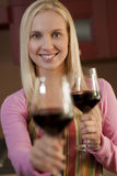 Offering a glass of wine. Young woman offering a glass of red wine in her kitchen Stock Image