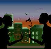She is offering her a special flower. Silhouettes of two girls meeting in evening on a cityscape background Stock Photo