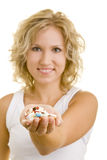 Offering medicine. Blonde woman holding many pills in her palm royalty free stock photo