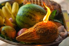 Offering for a temple with fruits and fire on coconut in metal t. Ray on Sri Lanka island Royalty Free Stock Photo