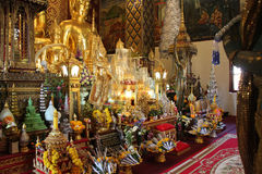 Offerings av blommor och guld- Buddhastatyer dekorerar en tempel (Thailand) Royaltyfria Bilder