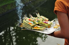 Offerings for the spirits. Balinese woman holding a tray with offerings and incense sticks for the spirits royalty free stock photos
