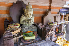 Offerings and Statue Perched on Top of a Temple in Bali. Balinese statue sits proudly at the top of a temple Stock Photos