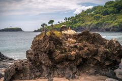 Offerings to the Balinese Hindu Gods and Demons placed on a coastal rock royalty free stock photo