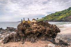 Offerings to the Balinese Hindu Gods and Demons placed on a coastal rock. `Perasi` Beach or `Pasir Putih royalty free stock photos