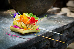 Offerings to gods in Bali. Traditional balinese offerings to gods in Bali with flowers and aromatic sticks Royalty Free Stock Photo